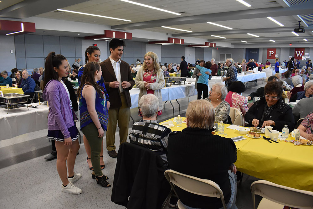 Members of the PWHS Colonial Players visit the 400+ seniors at the luncheon prior to the spring musical matinee.