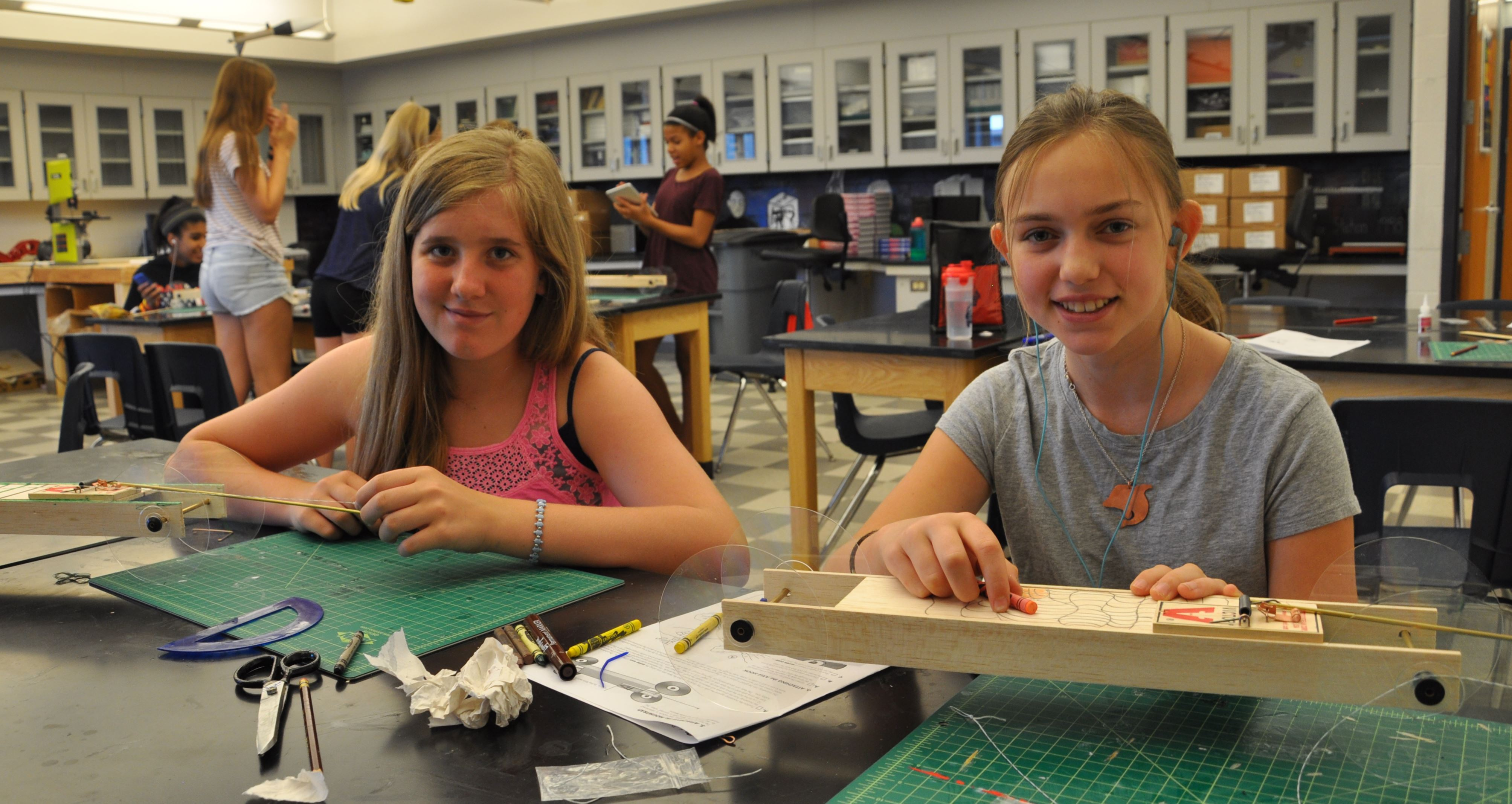Two girls at a table making mousetrap cars