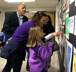 Elementary student shows parents her piece at the District Art Show.