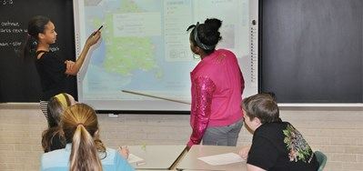 Two girls pointing to a map of France on an interactive whiteboard