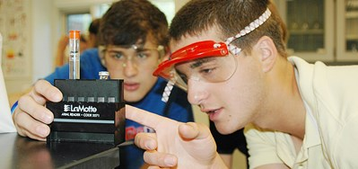 Two boys wearing goggles read a water testing tool in classroom