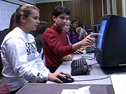 Boy pointing to girl's writing on a computer screen