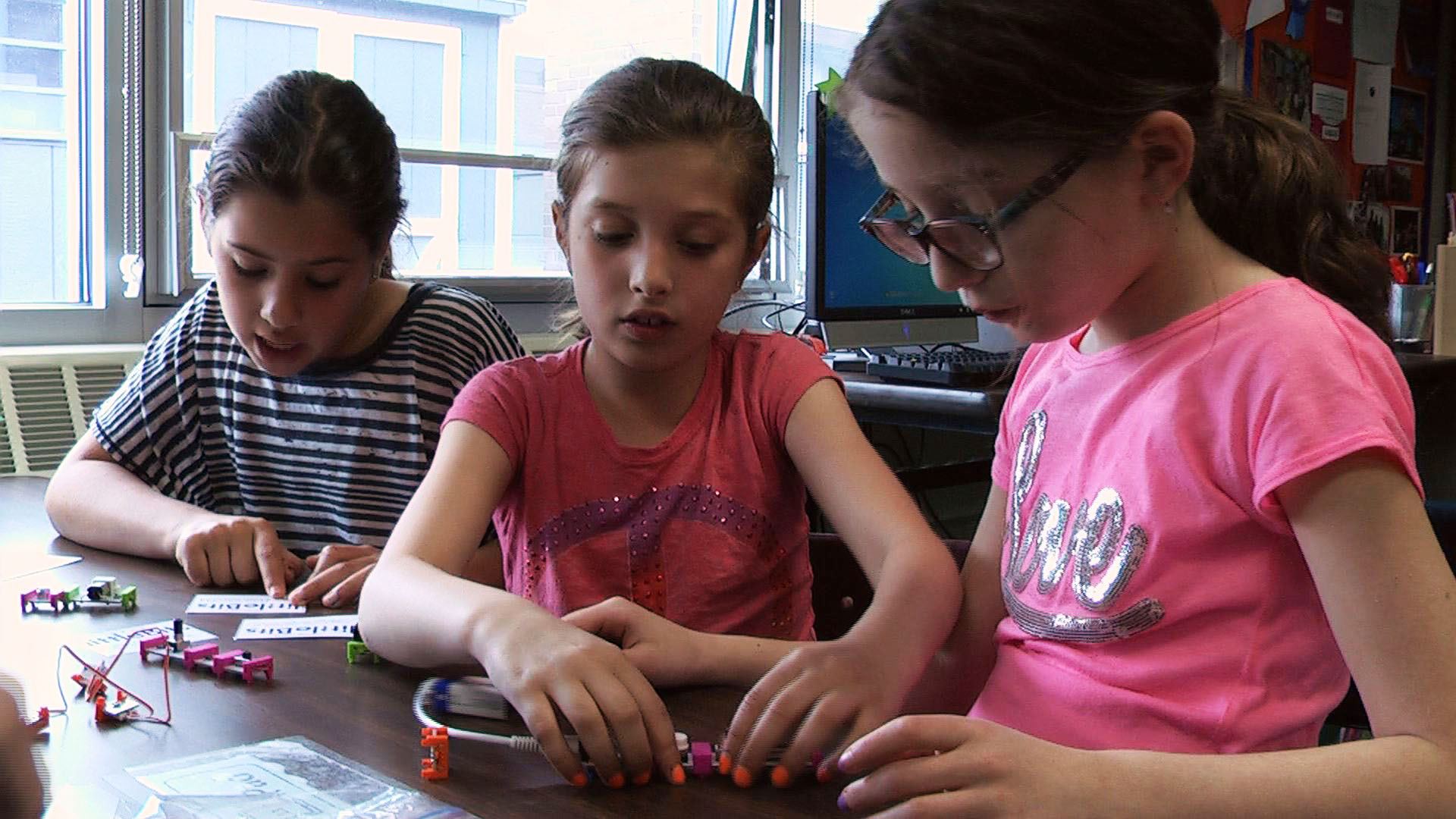 Three girls working together to create a simple circuit