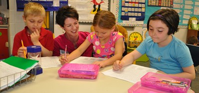 A parent helps elementary students with a language arts project