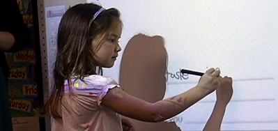 Elementary student writes on an interactive white board