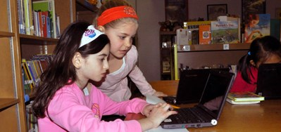 Two girls working together on a laptop
