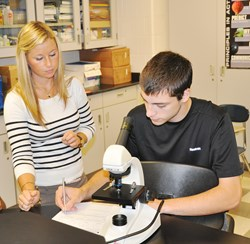 PWHS teacher works with a student in a science class