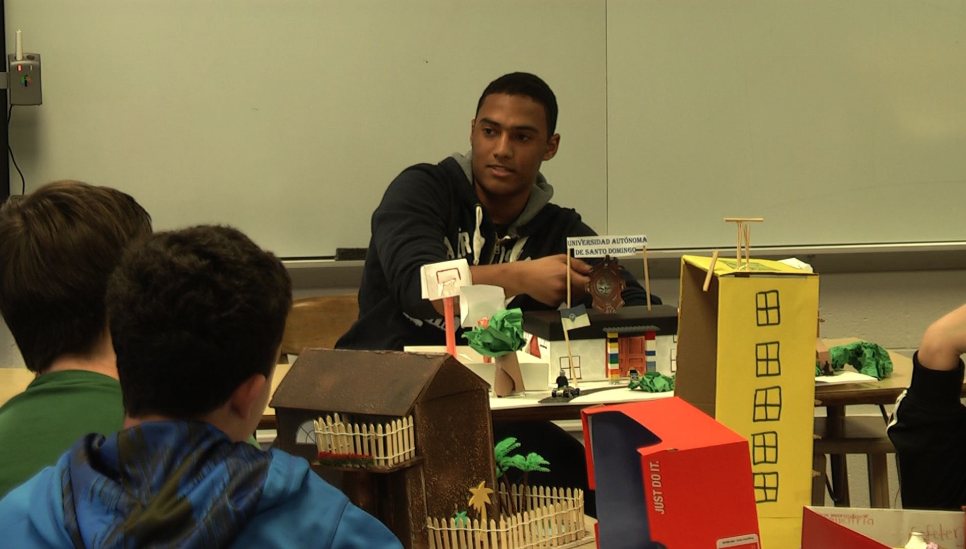 Boy at front of classroom describing a model of a building