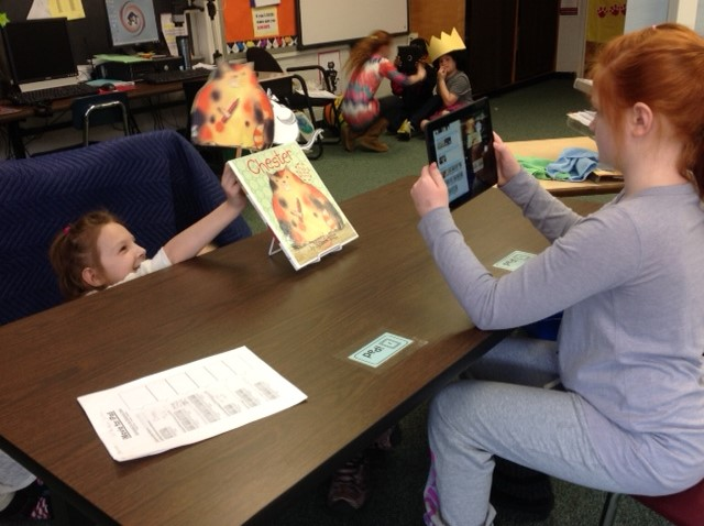 Third graders use an iPad to record a movie trailer about a book